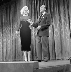 American actress and sex symbol Jayne Mansfield holds hands with American comedian and entertainer Jack Benny on the set of the 'Chrysler's Shower of...