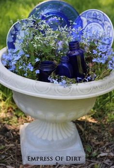 Blue and white plates and bottles in a garden planter to fill in until plants grow