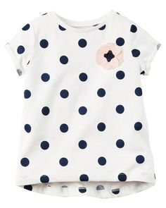 Featuring a polka dot print and rosette appliqué, this soft jersey tee is the perfect go-together with her favorite leggings for playground adventures.