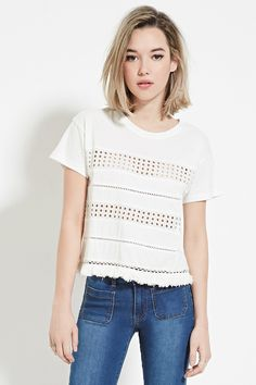 A knit top featuring front eyelet panels, front ladder-cutout crochet panels, short sleeves, and a tasseled hem.