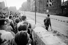 A crowd of West Berlin residents watches as an East German policeman patrols the Berlin Wall in August 1961.
