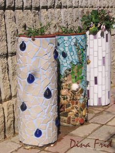 Mosaic potted plant cylinders made with PVC pipe. What a great and inexpensive idea to make those large plant stands that cost a fortune at garden centers. I'll be making some of these this spring for our deck.
