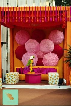 funky mehendi stage backdrop with umbrellas, yellow pink and red, parrot detailing, kitsch, offbeat, colorful, funky, destination wedding