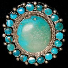 "This old silver and turquoise pin has a beautiful blue turquoise center stone that measures 1-1/4"" x 1-1/8"" that is surrounded by 19 small round turquoise stones each set in a silver bezel.  The pin is quite old and is in wonderful condition.  This is the style pin made by a Navajo for use by a Navajo to secure a manta or dress."