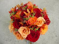 A mixture of three varieties of roses, wheat, berries and fall leaves.
