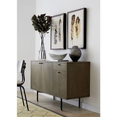 Mark Daniel's warm design makes a study of neutral grey-toned wood, industrial-inspired metal cross bar base and minimalist styling, achieving high marks for the sideboard's clean, structural feel. Sideboard features two adjustable shelves behind doors with cord cutouts and a drawer to store smaller items.