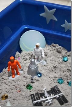 Moon sand in blue plastic bin.  Space theme sensory tub.