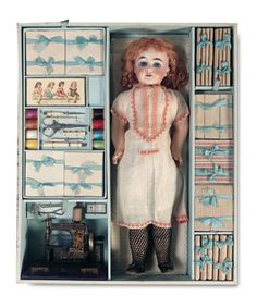 antique doll with silk ribbons, threads, bone sewing tools and scissors