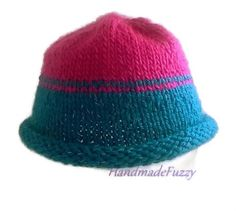 This beanie is hand knitted with a blue acrylic yarn that has a reflection thread woven in. The top of the hat is colored in fuchsia.   It is knitted in the…