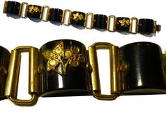 This is a jet black bakelite and brass link bracelet. Wearable length is 7. It is 3/4 wide. There are 7 links - 3 of them have a brass floral on-lay (of