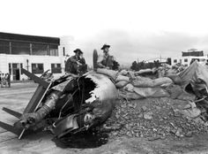 Two servicemen sit on the wreckage of a bomber, surrounded by dirt and sandbags in preparation for another wave of attackers. One looks through binoculars and the other smokes a cigarette.