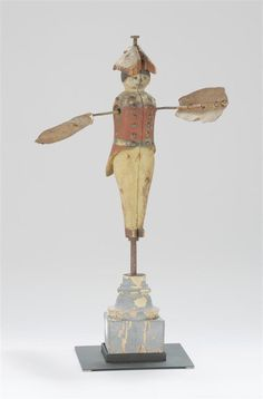 "Carved and painted wooden soldier-form Whirligig, Early 19th Century, with a red coat, blue belt and white pants. Coat with metal tack ornamentation, giving the appearance of buttons. Arms made from sheet metal with steel rod supports. Body supported by a metal rod attached to a turned wooden base. Height 20""."