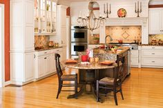 These homeowners created an island that has everything you need, including the kitchen sink. At one end, a countertop-height rectangle of granite offers plenty of prep space. One side boasts a wine rack and cabinet storage while the other holds trash, recycling, and the dishwasher. At the end, an attached round granite tabletop, supported by a pedestal stained to match the island, steps down to table height.