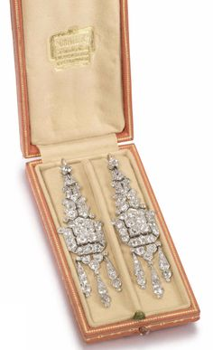 A pair of Art Deco diamond pendent earrings, by Cartier, circa 1925 Each elongated plaque, composed of articulated geometric motifs, pierced and set throughout with old brilliant and single-cut diamonds, terminating in a similarly-set diamond tassel, diamonds approximately 8.20 carats total, each signed Cartier London, length 6.7cm, maker's case