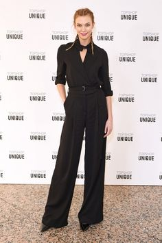 Karlie Kloss wears a button-down shirt, high-waisted trousers, and black pumps