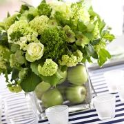 Nautical wedding centerpiece incorporating green hydrangeas and runner with navy and white stripes.