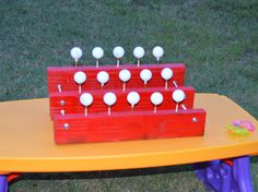 Ping Pong balls sat atop of golf tees which lie   in three 20' 2x4 boards fastened together with threaded rods.  Water guns were used to knock down each ping pong ball.