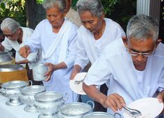 Serving white jasmine rice to monk's alms bowls during Buddhist Monk Blessing Ceremony for Health in old Age (Tor Ar Yu Health Blessing) in Nang Rong, Buriram area of Eastern Thailand (isan). Travel in Southeast Asia. http://live-less-ordinary.com/southeast-asia-travel/buddhist-monk-blessing-ceremony-thailand