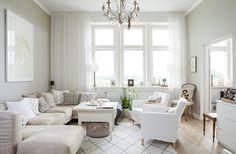 Olohuoneen tunnelma on pehmeän valkoinen. Vanha antiikkipöytä ja Stockmannilta hankittu kattokruunu ovat seuranneet mukana kodista toiseen.