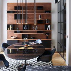 Une coin salle à manger avec une bibliothèque archi design en bois et une table tulipe en marbre noir et des fauteuils eames