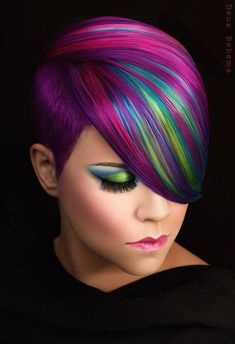 This purple & pink hair accented with blue & green by Erica Hardy-Knoop is truly one of the most fun & bold hair colors that I've ever seen! #haircolor #shorthair #purplehair