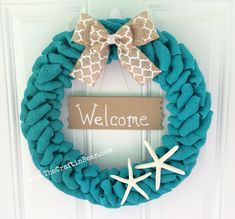 Handcrafted 19 teal burlap wreath with a white medallion print triple bow, hanging sand colored Welcome sign and two finger starfish accents. A