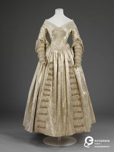 Cream figured silk satin wedding dress with silk net and lace trimming, England, 1841.
