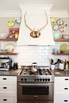 One of the things we love about this kitchen is how the builder/designer created this wall. The open shelving made out of walnut made us swoon. We hung up a plate wall, nailed some alters to the range hood, displayed more of kitchen goodies, and called it done. LOVE it.