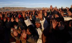 People hold their hands up to feel the first rays of sun during a traditional Andean new years' ritual at the ruins from the ancient civilization of Tiwanaku, Bolivia, on June 21, 2013. Bolivia's Aymara Indians celebrate the year 5,521 as well as the southern hemisphere's winter solstice, marking the start of a new agricultural cycle. (AP Photo/Juan Karita)