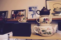 Three teapots stacked on top of each other in front of a wall of pictures. This picture is taken in the teashop - Ehsan & Pappas Tehus in Malmö, Sweden.