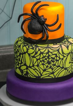 Make a fondant Halloween cake with spider webs and scary spider cake layon, totally on trend in orange, lime and purple.