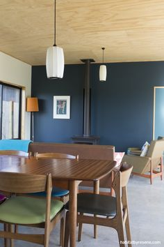Resene Elephant is a deep green-edged blue, used as a feature wall in the living room, and joined by a cavity sliding door in Resene Marathon. The chairs for the retro dining table were reupholstered in multi-colours by Anna. Photo by Marc Herbulot. Green Interior Design, Home Design Decor, Interior Design Inspiration, Home Decor, Dark Green Walls, Blue Walls, Wall Paint Colors, Interior Paint Colors, Dark Blue Feature Wall