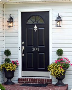 black painted front door; black lantern porch lights; large urns with geraniums, million bells, and topiary