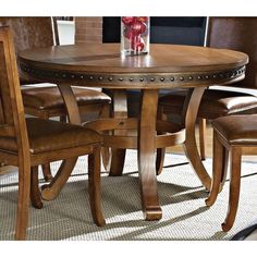 The Old World, colonial style of the Bramley dining table is evident in the wood plank style top accented with nailhead trim around the apron. The decorative leg pedestal features four curved legs with a round stretcher for added stability.
