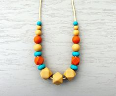 Silicone Necklace Mustard Pumpkin  Emerald. This nursing + teething necklace is a functional and stylish addition to mom's wardrobe. This handmade necklace features a bold color palette of warm pumpkin + mustard yellow with pops of bright emerald green. This sensory necklace serves as a playful distraction for a nursing baby, something fun to 'nom on for a teething baby and something pretty for mom to wear. Made with 100% NON-TOXIC food grade silicone, silky nylon cord + a break-away clasp.