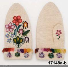 Ett par mansvantar a-b, av vitt ullgarn, nålbundna och sedan valkade.  På handryggen broderade med ullgarn, blommorna i plattsöm med konturer i kedjesöm troligen utfört med virknål. på tummen en ensam rosa blomma, Den nedvikta kragen kantad med tät kort kavelfrans och kragen  har med jämna mellanrum små tofsar i blandade färger.  Kallas lokalt för Dalbyvantar och användes av både män och kvinnor.