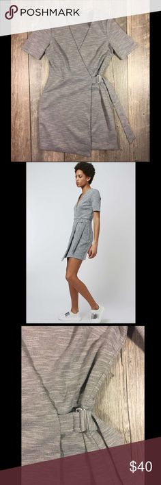 TopShop gray belted wrap mini dress TopShop gray belted wrap mini dress. Snap insides and belted. structured wrap dress for now. With a short sleeve design and flattering belted wrap silhouette, wear with heels and a minmal accessories to finish the look. 96% Polyester, 4% Elastane. Machine wash. 35 inches at longest. Tag reads US size 6. Topshop Dresses