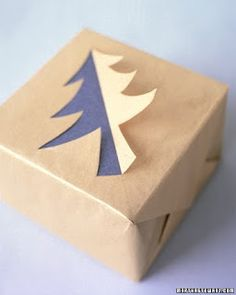 A pine-tree profile cut into gold tissue paper folds back to reveal a layer of silver tissue beneath