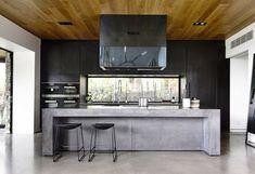 Schwarze Küche mit Elementen aus Beton und Holz