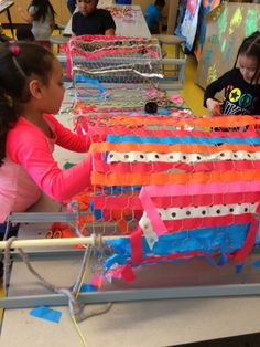 Kindergarten collaborative weaving ribbons on chicken wire. Image only.