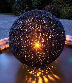 Dark Planet contemporary spherical garden art glowing at night