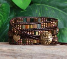 This four wrap bracelet features 5x5mm Miyuki Tila Beads, in gorgeous shades of bronze and iridescent greens, meticulously ladder-stitched on to top quality, dark brown Distressed Leather. Made by Miyuki, the oldest and finest manufacturer of Japanese seed beads, Tila Beads are a beautiful flat glass bead with various finishes, and one of the newest bead shapes available (and I love, love, love them!) In this bracelet, they are complimented by Miyuki Opaque Seed Beads, and completed with a…