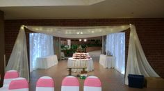 White Chair Covers with Red Organza Sashes, White Table Skirting, White Door Drape, White Pipe and Drape with Light Curtains at Garden Room by Deckci Decor