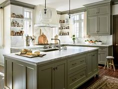 A kitchen naturally has a lot of hard surfaces—in this case, a stainless-steel range and slab marble countertops and backsplashes. A true warm gray on the cabinets—and on the crown molding ringing the room—helps soften those elements while unifying the space and complementing the wood floor, door, and accessories says interior designer Barbara Westbrook. Paint: Benjamin Moore's Galveston Gray