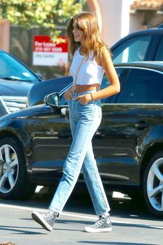 Kaia Gerber wore a classic look featuring Converse Chuck Taylor sneakers, jeans, and a white crop top. This outfit will never go out of style.