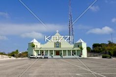 Pale Green Church - A pale green church with smooth walls and white pillars with people lounging on the steps and three cars with an empty parking lot stretched in the foreground located in Turks and Caicos.