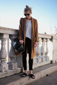 striped tee, black cuffed ankle jeans, camel coat, bun, and of course - frumpy casual slides [normcore]
