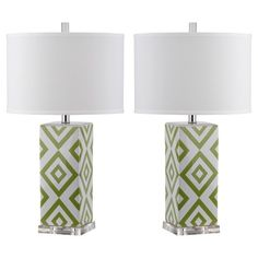Bring eye-catching style to your home with the Safavieh Parker Table Lamp Set Of 2. Made of glossy ceramic, these table lamps have cubical bodies printed with a geometric diamond pattern. Each lamp has a clear acrylic base and a white cotton lamp shade in a drum shape. Clear rod finials add the final touch of modern style. Set includes 2 lamps.
