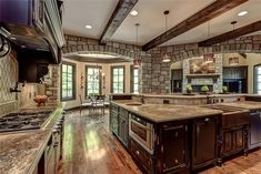 Large kitchen with stone features opens up to dining area. Custom dark wood cabinetry. How awesome is this design?!  #kitchen #stone #cabinetry
