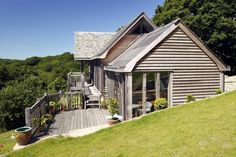 Nestled into a steep site this imaginatively designed barn house is 'upside-down' to take advantage of the stunning views over the Helford river in Cornwall. The first floor open plan living rooms are set into a canopy of old oak trees. Other features include arch braced trusses, extensive balconies and a spiral staircase.